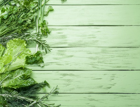 green vegetables: Green herbs on the green wooden background.