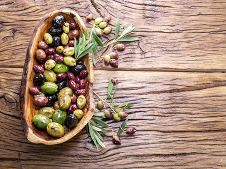 oilcan: Whole table olives in the wooden bowl on the table. Stock Photo