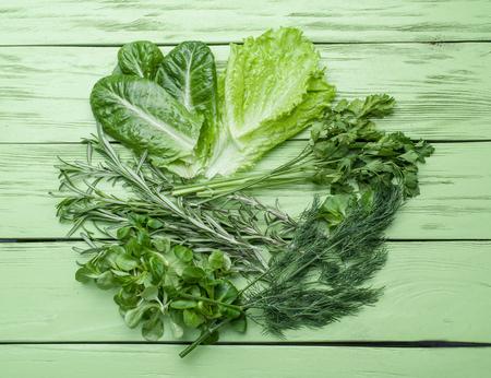 légumes verts: herbes vertes sur le fond en bois vert.