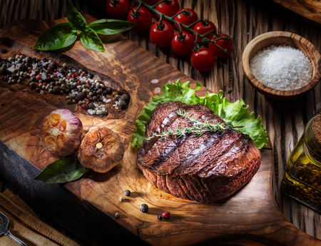 Beef steaks with spices on a wooden tray. Barbecue food. Standard-Bild