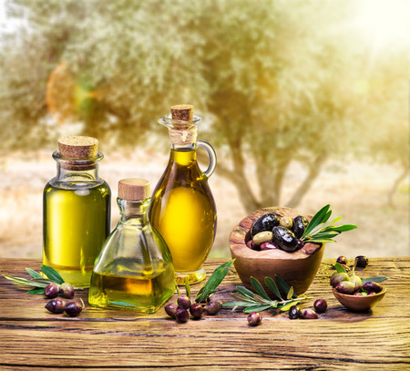 aceite oliva: El aceite de oliva y las bayas est�n en la mesa de madera bajo el olivo.