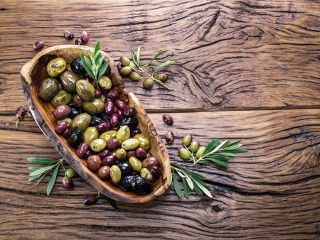 vegetarian food: Whole table olives in the wooden bowl on the table. Stock Photo