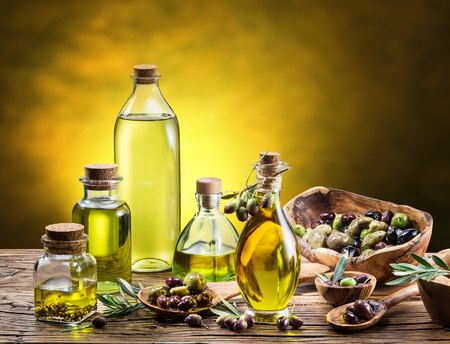 aceite de oliva: Glass bottles of olive oil and few berries on the wooden table. Studio shot.