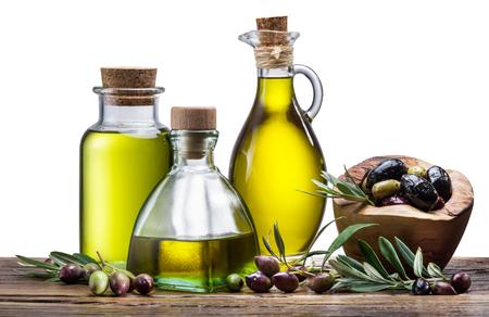 aceite de oliva: aceite de oliva y las bayas en la mesa de madera. Fondo blanco. El fichero contiene trazados de recorte.