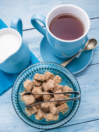 cup of tea: Cup of tea, milk jug and cane sugar cubes on old blu wooden table.