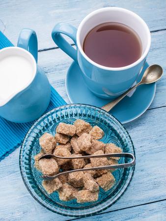 taza de té: Taza de té, jarra de leche y cubos de azúcar de caña en tabla de madera azul.