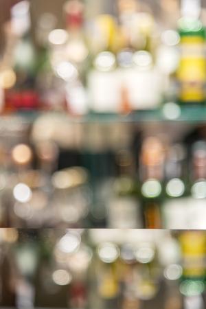 alcool: Verre comptoir de bar avec des étagères floues avec des bouteilles d'alcool sur le fond.