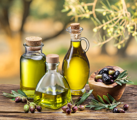 oilcan: Olive oil and berries are on the wooden table under the olive tree.