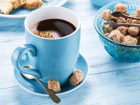 copa: Taza de café, jarra de leche, cubos de azúcar de caña y fruta-torta en la vieja mesa de madera azul.