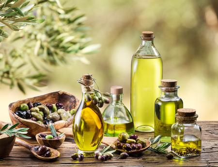 aceite de oliva: El aceite de oliva y las bayas están en la mesa de madera bajo el olivo.