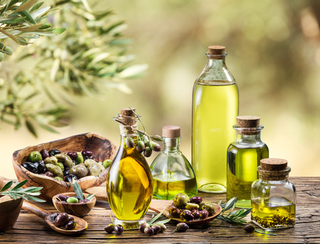 sun oil: Olive oil and berries are on the wooden table under the olive tree.