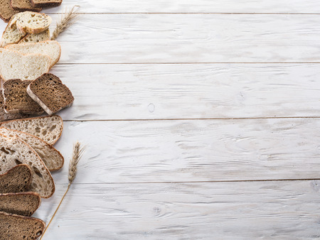 rye: Different types of sliced bread on wooden background. Stock Photo