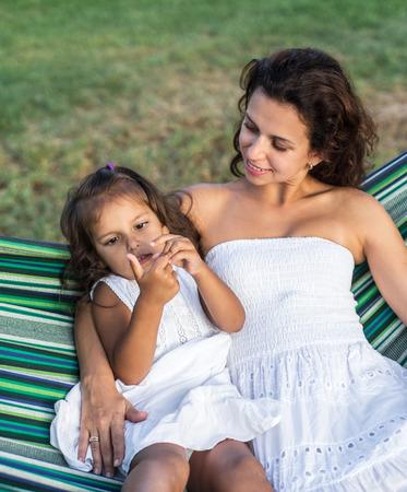 niños sentados: Madre e hija están descansando en el campo.