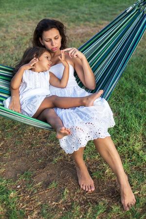 mujer hijos: Madre e hija están descansando en el campo.