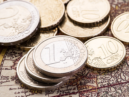 old world: Euro coins over the old world map. Macro picture.