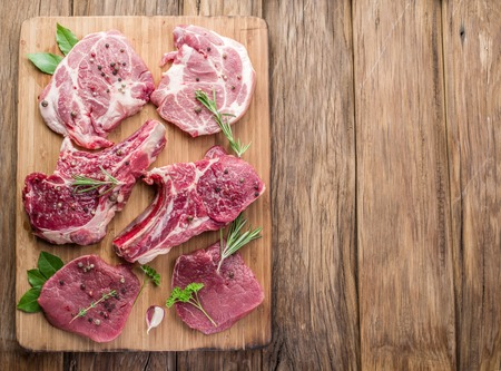 wood board: Raw meat steaks with spices on the wooden cutting board. Stock Photo