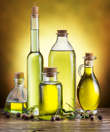Glass bottles of olive oil and few berries on the wooden table. Studio shot.