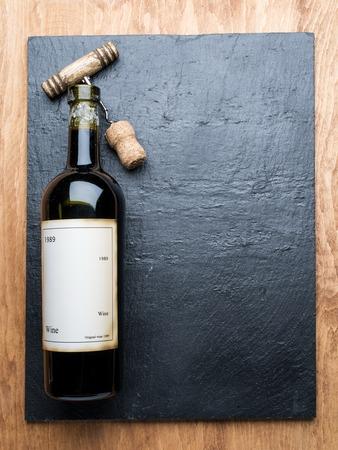 grafit: Wine bottle and corkscrew on the graphite board. Zdjęcie Seryjne
