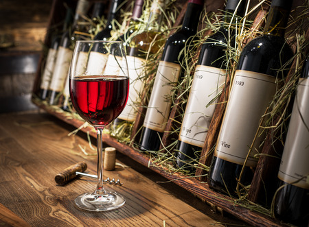 test glass: Glass of red wine and wine bottles on the background. Stock Photo