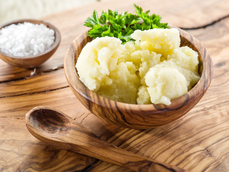pure de papas: Puré de patatas en el recipiente de madera sobre la bandeja de servicio.
