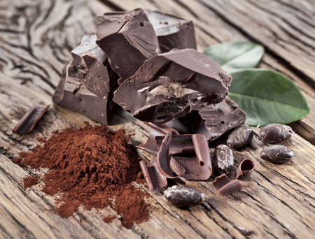 cocoa bean: Chocolate and cocoa bean over wooden table. Stock Photo