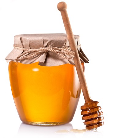 wooden stick: Glass can full of honey and wooden stick on a white background.