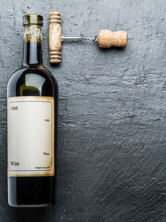 red wine stain: Wine bottle and corkscrew on the graphite board. Editorial