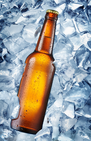 moisture: Cold bottle of beer in the ice cubes. There is condensated moisture over glass. Stock Photo