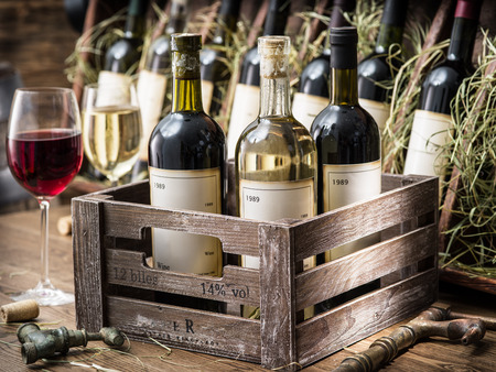 Old wine bottles in a wooden crate. Stock Photo
