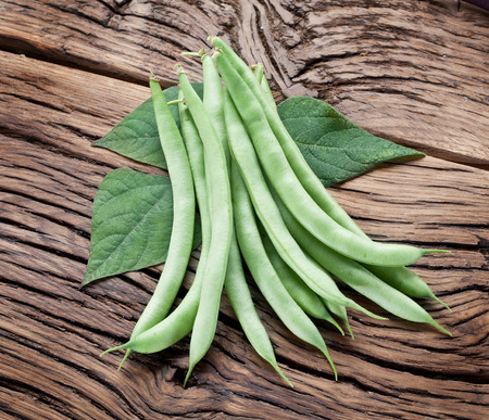 leguminous: Fresh green beans on the old wooden table.