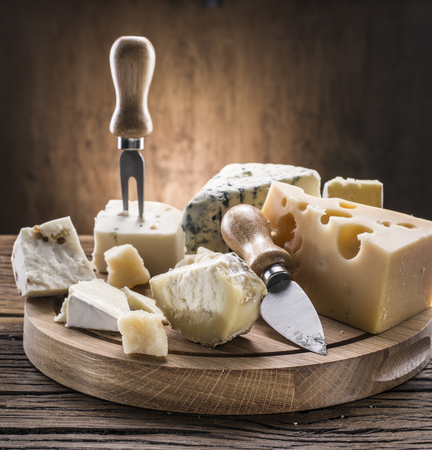 Variety of cheeses on a wooden board.