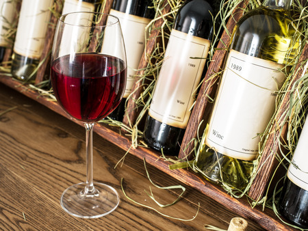 wine testing: Glass of red wine and wine bottles on the background. Editorial