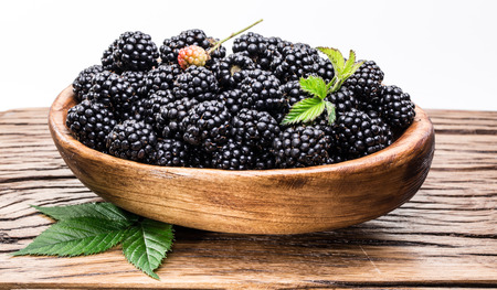 outs: Blackberries in the wooden bowl on the table. Stock Photo