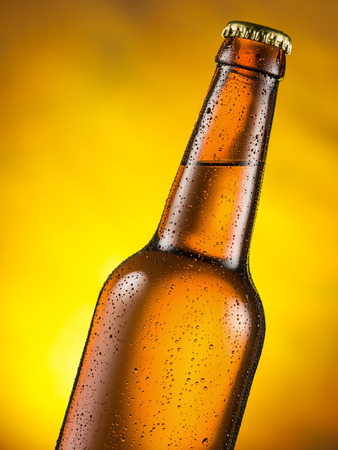 moisture: Cold bottle of beer with condensed moisture on it. Yellow background. Stock Photo