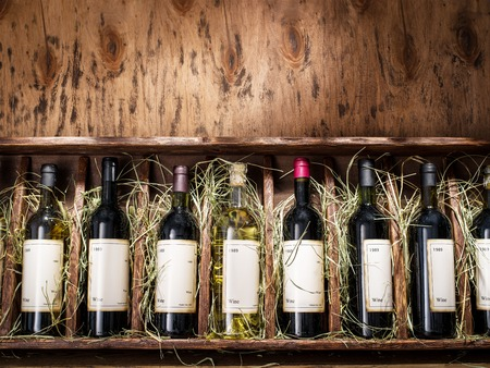 Wine bottles on the wooden shelf. Archivio Fotografico
