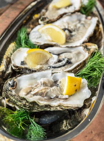 Opened oysters with piece of lemon on the cooper tray. Stock Photo
