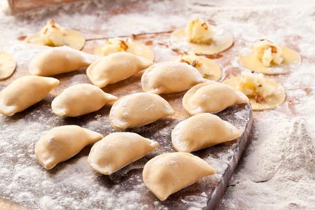 pierogi: Vareniki (dumplings) with potatoes and onion. Uncooked on the wooden desk. Stock Photo
