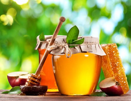 Glas blikken vol met honing en appels op oude houten tafel in de tuin.