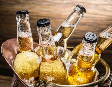 Koude flessen bier in de koperen emmer op de houten tafel.