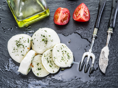 Mozzarella and tomatoes. Dark grey background.