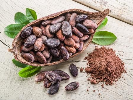 Cacao poeder en cacao bonen op de houten tafel. Stockfoto