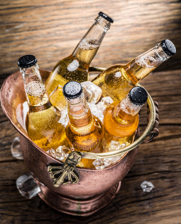 alcohol drinks: Cold bottles of beer in the brazen bucket on the wooden table.