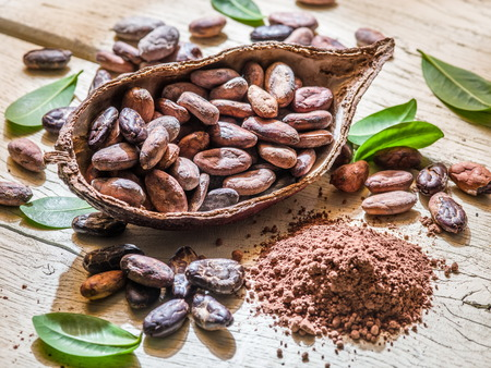 Cocao powder and cocao beans on the wooden table. Imagens - 53789137