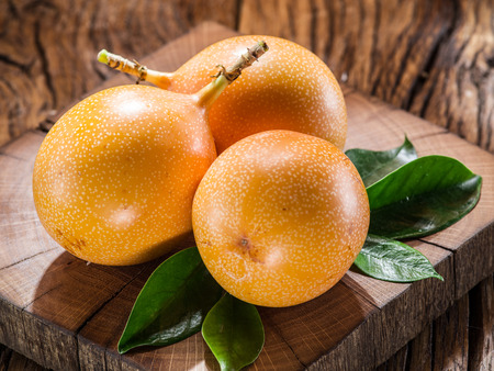 wooden table: Granadilla fruits on the wooden table. Stock Photo