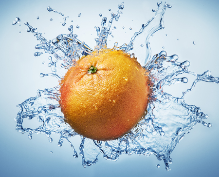 Grape-fruit surrounded with water splash.