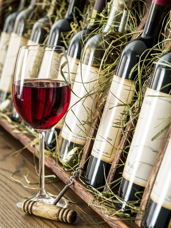 wine testing: Glass of red wine and wine bottles on the background. Stock Photo
