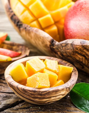 ripe: Pieces of mango fruit in the wooden bowl.