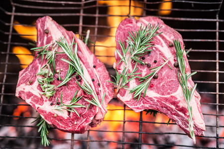 spicy cooking: Rib eye steaks and grill with burning fire behind them. Stock Photo