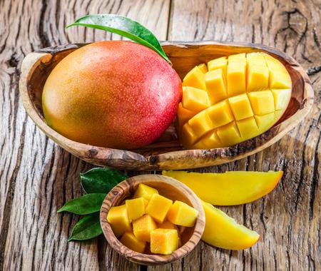 Mango fruit and mango cubes on the wooden table. Banco de Imagens - 54521941