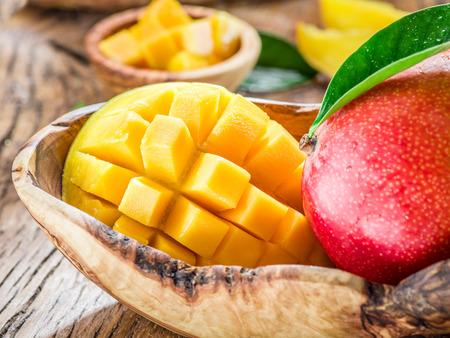 mango: Mango fruit and mango cubes on the wooden table.
